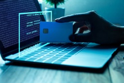 The concept of credit card theft. Hackers with credit cards on laptops use these data for unauthorized shopping. Unauthorized payments from credit card owners. In the hacker's secret office