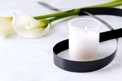 The concept of death and grief. Mourning candle on a concrete background next to white flowers. Copy space