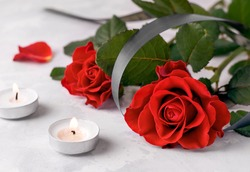 The concept of death and sorrow. Bouquet of fresh red roses next to two mourning candles on a white background