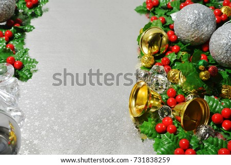The concept of decorations in the Christmas Eve. Holly fruit on silver paper background with copy space for your text. Sensitive focus.