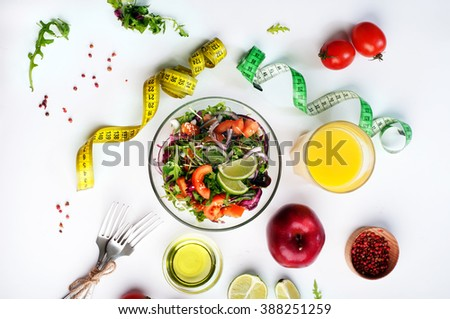 The concept of dietetic vegetarian food. Salad with arugula, tomatoes and onions, close to orange juice, apple and measuring tape, which symbolizes the reduction in volume of the body. Сток-фото ©