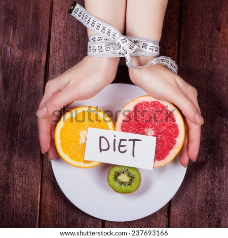 The concept of eating disorders: bulimia, anorexia, diet fads. Women\'s hands tied centimeter. Girl\'s hands with a plate and fruit. Fruit diet. Low-fat diet.