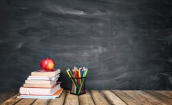 The concept of education, stack of books, an apple, pencils against the background of the school blackboard