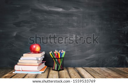 The concept of education, stack of books, an apple, pencils against the background of the school blackboard Foto d'archivio ©