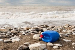 The concept of environmental protection and ecology. A blue plastic canister with a red cork lies on the seashore.