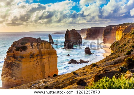 The concept of exotic, active and photo-tourism. Rocks of the Twelve Apostles at sunset. Powerful Pacific surf breaks down on the shore. Grandiose coast of Australia