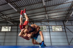 The concept of fair wrestling. Two greco-roman  wrestlers in red and blue uniform wrestling   on a wrestling carpet in the gym.