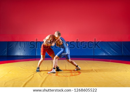 The concept of fair wrestling. Two greco-roman  wrestlers in red and blue uniform wrestling   on a yellow wrestling carpet in the gym