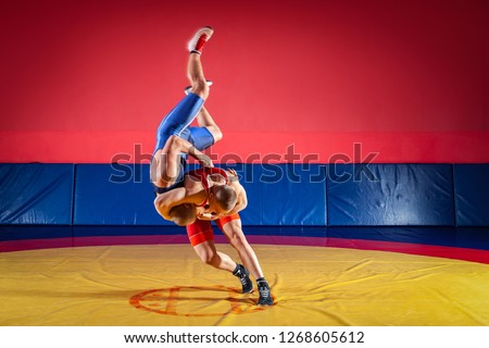 The concept of fair wrestling. Two young men in blue and red wrestling tights are wrestlng and making a suplex wrestling on a yellow wrestling carpet in the gym