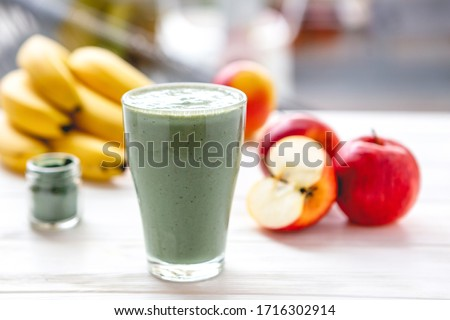 The concept of food and drink, diet and nutrition. Healthy green vegan smoothie with banana, spirulina and ripe apple for summer detoxification Foto stock ©