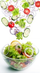 The concept of freshly prepared vegan salad. Fresh ingredients for a salad, such as tomatoes, purple onion, cucumber slices and lettuce, which fall in a bowl with salad. Vegetarian concept