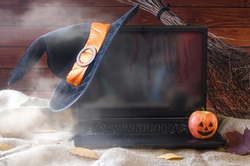 The concept of Halloween: a laptop, a witch hat and a broom, free space for your advertising. Halloween background, sale of goods.
