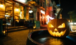 The concept of Halloween. Pumpkin with a face stands on the street and decorates the street scaring passers-by people.