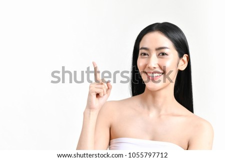The concept of healthy beautiful woman. Beautiful women keep healthy. Beautiful women take care of skin health. Beautiful women are thinking about beauty. Beauty Asian girl is pointing fingers. #1055797712