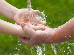 The concept of heritage and nature conservation on Earth.Water pours into the hands of a child in the hands of an older grandmother against a background of green grass.