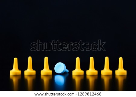 The concept of individuality. Blue board game figure fell out of row of yellow figures