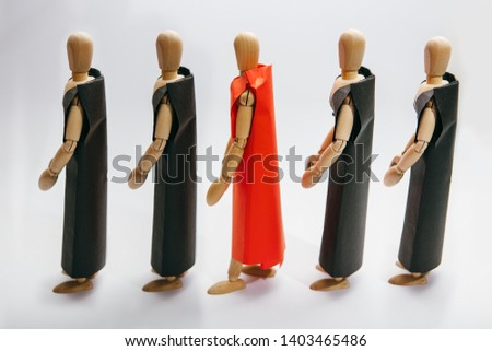 The concept of individuality, creative, unique thinking.  Wooden mannequins stand in black  and one in red.