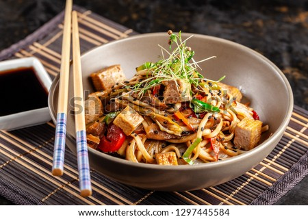 The concept of Japanese cuisine. Chinese noodles with chicken, grilled vegetables, and tofu in unagi sauce. Serving Asian dishes in the restaurant in a plate on a bamboo mat. Top view, copy space