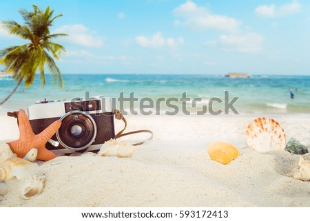 The concept of leisure travel in the summer on a tropical beach seaside. retro camera on the sandbar with starfish, shells, coral on sandbar and blur sea background.  vintage color tone styles. #593172413