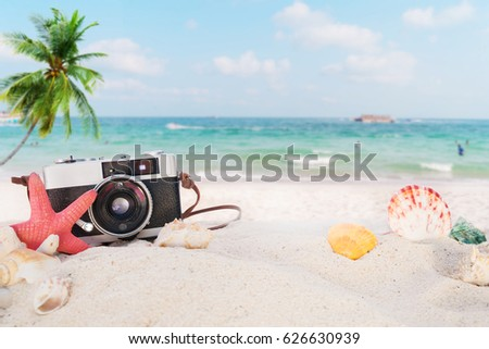 The concept of leisure travel in the summer on a tropical beach seaside. retro camera on the sandbar with starfish, shells, coral on sandbar and blur sea background.  vintage color tone styles. #626630939