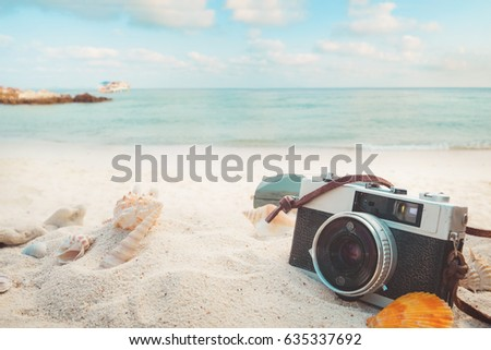 The concept of leisure travel in the summer on a tropical beach seaside. retro camera on the sandbar with starfish, shells, coral on sandbar and blur sea background.  vintage color tone styles. #635337692