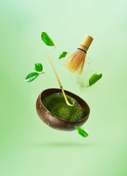 The concept of levitation of making matcha green tea. Flying tea leaves, matcha powder, bamboo whisk, spoon.