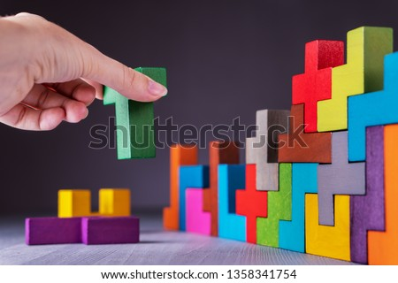 The concept of logical thinking. Geometric shapes on a gray background. Hand holding wooden puzzle element. Hand sets the element of the puzzle. Business building concept. #1358341754