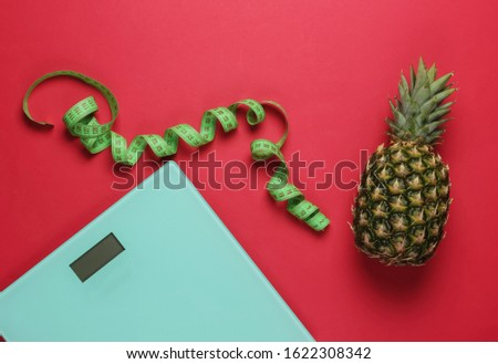 The concept of losing weight. Scales, pineapple with measuring tape on red background. Healthy eating. Top view