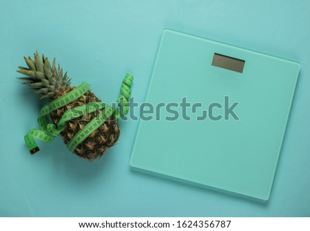 The concept of losing weight. Scales, pineapple wrapped with measuring tape on blue pastel background. Healthy eating. Top view