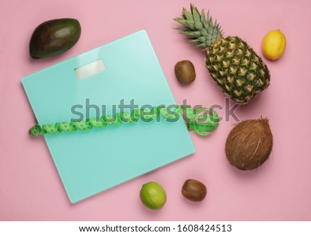 The concept of losing weight. Scales, ruler, tropical fruits on pink pastel background. Healthy eating. Top view