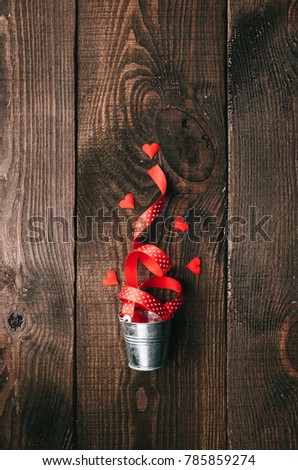the concept of love and caring for a loved one. Knitted hearts and decorative buckets on a wooden background #785859274