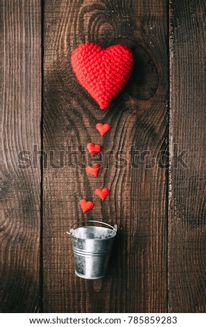 the concept of love and caring for a loved one. Knitted hearts and decorative buckets on a wooden background #785859283