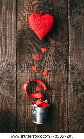 the concept of love and caring for a loved one. Knitted hearts and decorative buckets on a wooden background #785859289