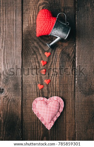 the concept of love and caring for a loved one. Knitted hearts and decorative buckets on a wooden background #785859301