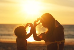 The concept of love, parenthood and a happy family. Mother and child daughter show heart from hands at sunset on beach