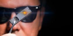 The concept of military artificial intelligence and espionage. A man in black glasses holds a microchip.