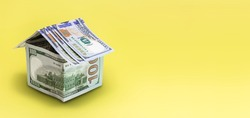 The concept of mortgage and rental housing and real estate. Mortgage credit lending. House made of dollar bills on a yellow background