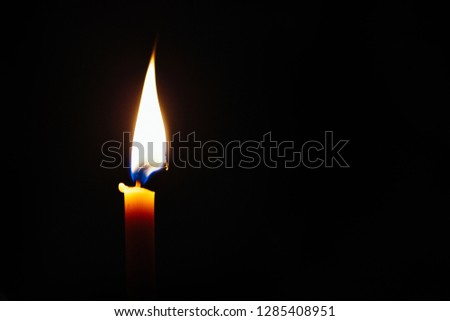 The concept of mourning, grief or sorrow. One candle light burning in the black background with copy space. Candle flame