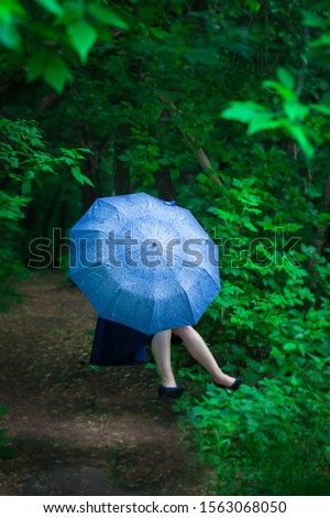 The concept of mystery. The girl hid behind a blue umbrella. Woman levitates.