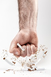 The concept of nicotine addiction and anti-Smoking. A man's fist smashes the cigarettes, and the tobacco flies apart. White background. Vertical orientation