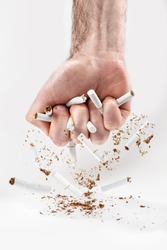 The concept of nicotine addiction and anti-Smoking. A man's fist squeezes the cigarettes, breaking them into small pieces. White background. Vertical. Copy space