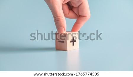 The concept of opposites, hand choose wood blog with plus and minus on blue background, copy space. Stockfoto ©