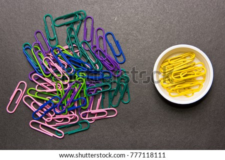 The concept of order and chaos. Chaotic disorganized colorful paper clips and to order the yellow paper clip
