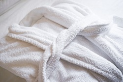 The concept of rest in a hotel. White terry bathrobe on bed in bedroom close-up.
