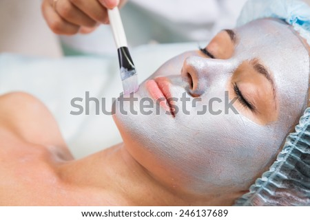 The concept of skin care. Application of special anti-aging masks. A young girl in a beauty salon. Beautician Apply the mask on the face of the model.