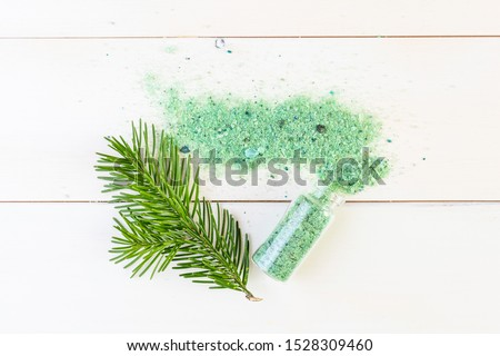 The concept of spa, relaxation, organics. Transparent bottle with sea salt and spruce branch on a light wooden background. Organic apothecary. Place for text. Minimalism.