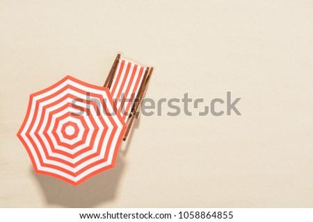 The concept of summer vacation. Top view on a sun lounger under an umbrella on the sandy beach