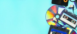 The concept of the evolution of music. Cassette, CD-disk, mp3 player on blue background. Vintage and modernity. Music support. Banner