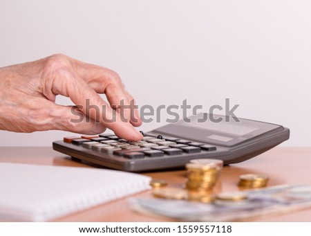 The concept of the financial life of senior citizens. The budget of an elderly person. An elderly woman considers the amount of money on a calculator.