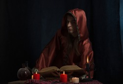 The concept of the office of a medieval alchemist: a magician in a red robe with a hood sits at a table and holds an old folio, surrounded by burning candles, dusty glass vessels, in the semi-darkness